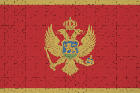 Montenegro flag  is depicted on a folded puzzle Фото со стока