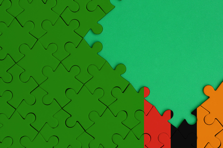 Zambia flag  is depicted on a completed jigsaw puzzle with free green copy space on the right side.