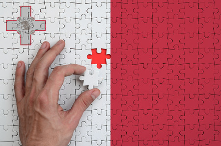 Malta flag  is depicted on a puzzle, which the man's hand completes to fold.