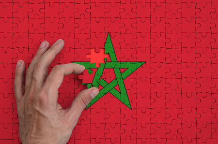 Morocco flag  is depicted on a puzzle, which the man's hand completes to fold.