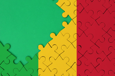 Mali flag  is depicted on a completed jigsaw puzzle with free green copy space on the left side.