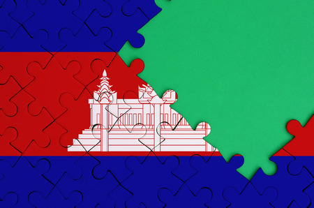 Cambodia flag  is depicted on a completed jigsaw puzzle with free green copy space on the right side.