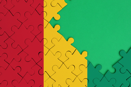 Guinea flag  is depicted on a completed jigsaw puzzle with free green copy space on the right side.