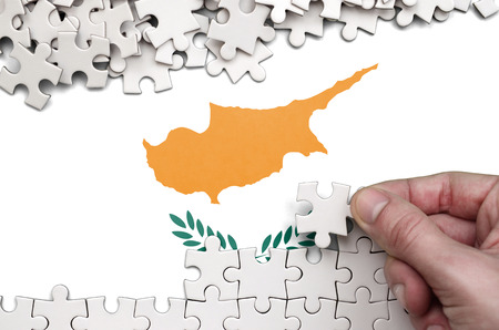Cyprus flag  is depicted on a table on which the human hand folds a puzzle of white color. 免版税图像