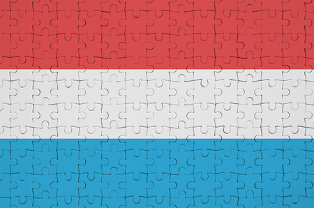 Luxembourg flag  is depicted on a folded puzzle Foto de archivo