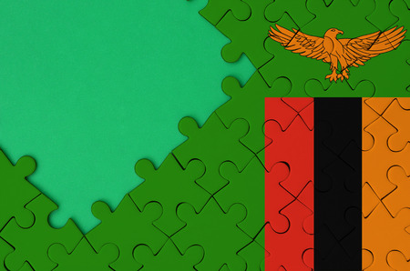 Zambia flag  is depicted on a completed jigsaw puzzle with free green copy space on the left side. Stock Photo