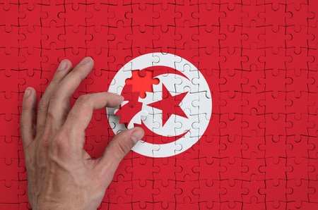Tunisia flag  is depicted on a puzzle, which the man's hand completes to fold. Stok Fotoğraf