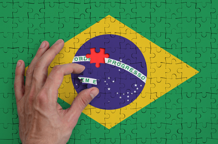 Brazil flag  is depicted on a puzzle, which the man's hand completes to fold. Banco de Imagens