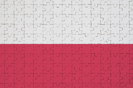 Poland flag  is depicted on a folded puzzle 免版税图像