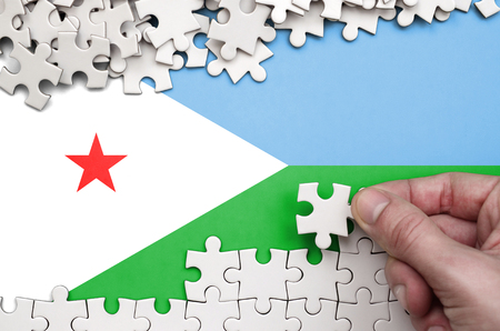 Djibouti flag  is depicted on a table on which the human hand folds a puzzle of white color.