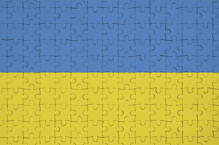 Ukraine flag  is depicted on a folded puzzle Stock Photo