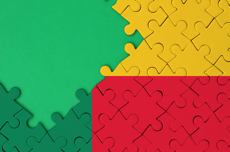 Benin flag  is depicted on a completed jigsaw puzzle with free green copy space on the left side.