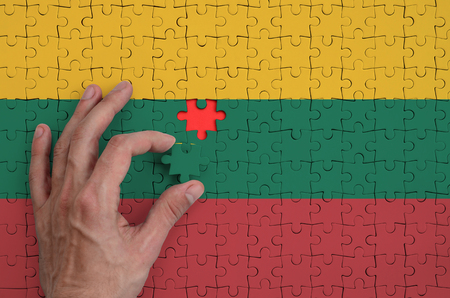 Lithuania flag  is depicted on a puzzle, which the man's hand completes to fold.
