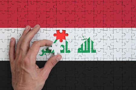 Iraq flag  is depicted on a puzzle, which the man's hand completes to fold.