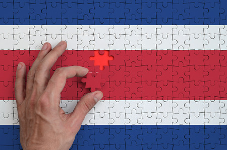 Costa Rica flag  is depicted on a puzzle, which the man's hand completes to fold. Stok Fotoğraf