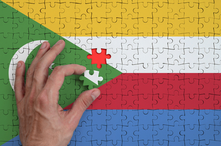 Comoros flag  is depicted on a puzzle, which the man's hand completes to fold.