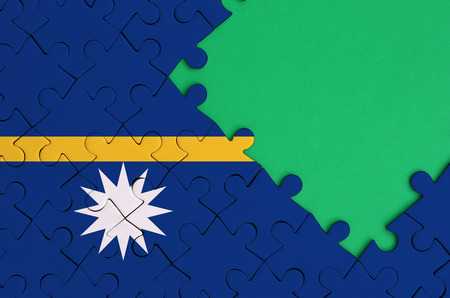 Nauru flag  is depicted on a completed jigsaw puzzle with free green copy space on the right side. Stock Photo