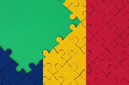 Chad flag  is depicted on a completed jigsaw puzzle with free green copy space on the left side.