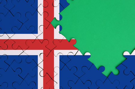 Iceland flag  is depicted on a completed jigsaw puzzle with free green copy space on the right side.