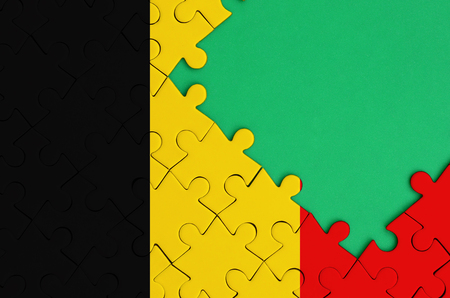 Belgium flag  is depicted on a completed jigsaw puzzle with free green copy space on the right side. Stock Photo