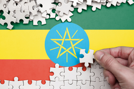 Ethiopia flag  is depicted on a table on which the human hand folds a puzzle of white color.