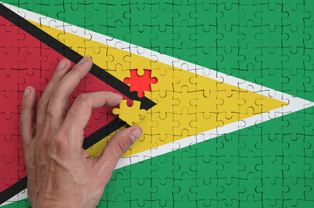Guyana flag  is depicted on a puzzle, which the mans hand completes to fold. Stock Photo
