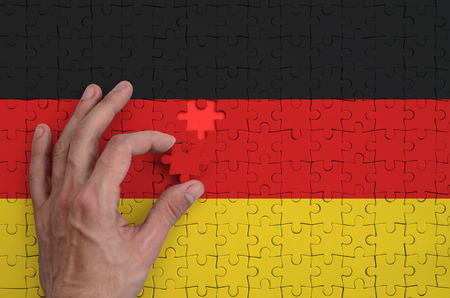 Germany flag  is depicted on a puzzle, which the mans hand completes to fold.