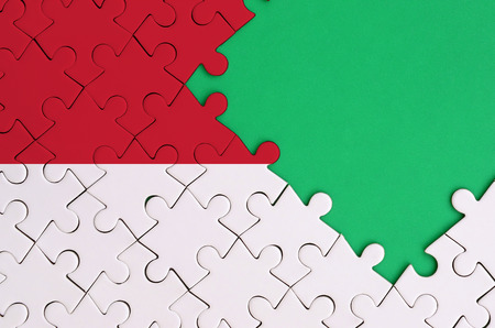 Indonesia flag  is depicted on a completed jigsaw puzzle with free green copy space on the right side.