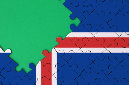 Iceland flag  is depicted on a completed jigsaw puzzle with free green copy space on the left side.