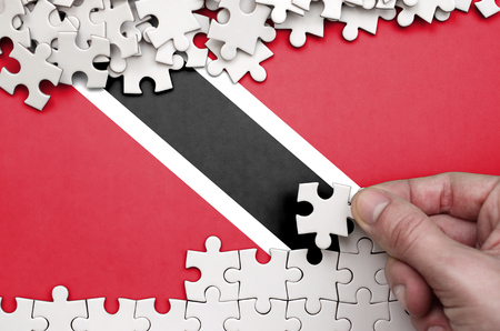 Trinidad and Tobago flag  is depicted on a table on which the human hand folds a puzzle of white color.