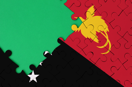 Papua New Guinea flag  is depicted on a completed jigsaw puzzle with free green copy space on the left side. Stock Photo