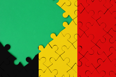 Belgium flag  is depicted on a completed jigsaw puzzle with free green copy space on the left side.
