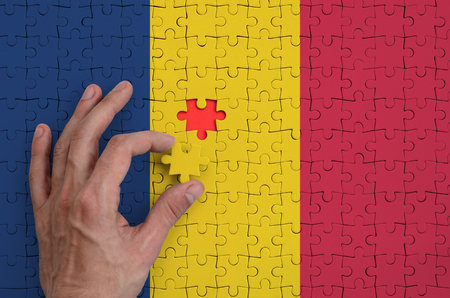 Chad flag  is depicted on a puzzle, which the mans hand completes to fold. Фото со стока
