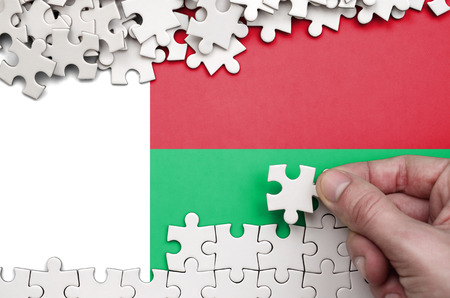 Madagascar flag  is depicted on a table on which the human hand folds a puzzle of white color. 免版税图像