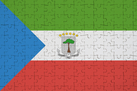 Equatorial Guinea flag  is depicted on a folded puzzle Imagens