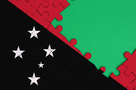 Papua New Guinea flag  is depicted on a completed jigsaw puzzle with free green copy space on the right side.