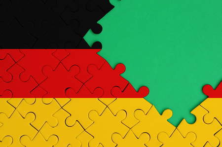 Germany flag  is depicted on a completed jigsaw puzzle with free green copy space on the right side.