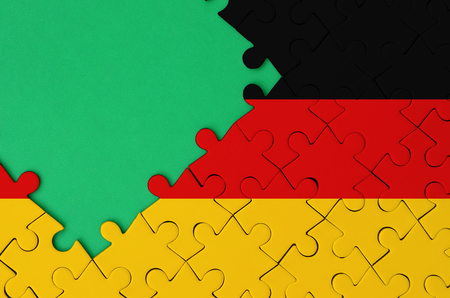 Germany flag  is depicted on a completed jigsaw puzzle with free green copy space on the left side. Stock Photo