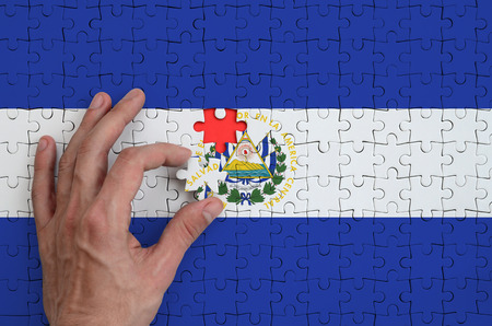 El Salvador flag  is depicted on a puzzle, which the man's hand completes to fold.