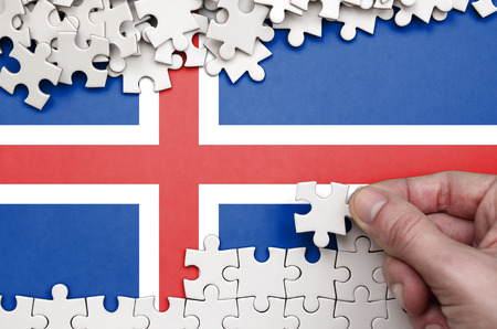 Iceland flag  is depicted on a table on which the human hand folds a puzzle of white color. Banco de Imagens