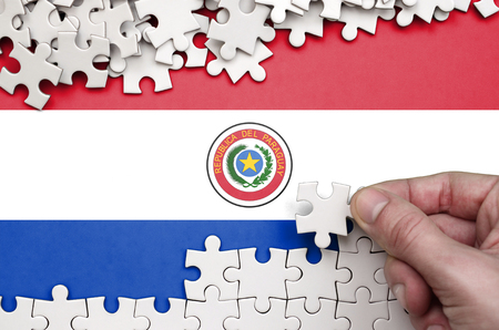 Paraguay flag  is depicted on a table on which the human hand folds a puzzle of white color. 免版税图像