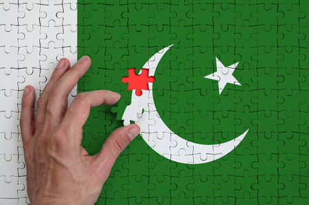 Pakistan flag  is depicted on a puzzle, which the mans hand completes to fold.