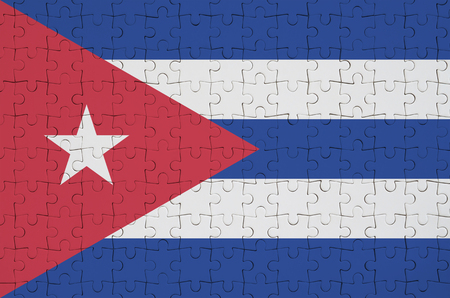 Cuba flag  is depicted on a folded puzzle Imagens