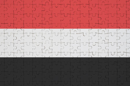 Yemen flag  is depicted on a folded puzzle Imagens - 101885850