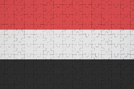 Yemen flag  is depicted on a folded puzzle Banco de Imagens
