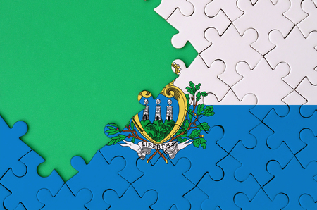 San Marino flag  is depicted on a completed jigsaw puzzle with free green copy space on the left side.