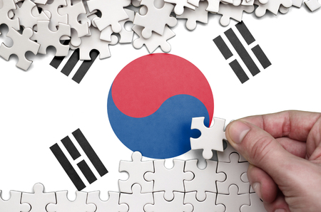 South Korea flag  is depicted on a table on which the human hand folds a puzzle of white color.