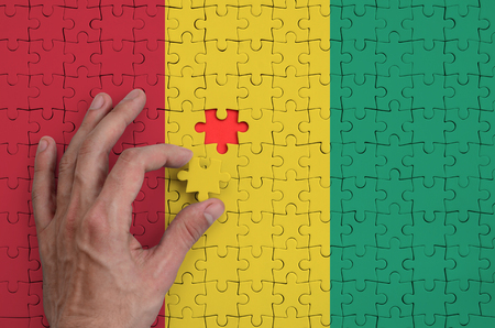 Guinea flag  is depicted on a puzzle, which the man's hand completes to fold.
