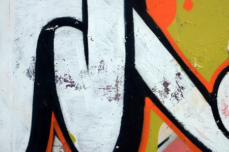 Street art. Abstract background image of a fragment of a colored graffiti painting in white and orange tones.