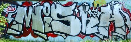 Sztuka uliczna. Abstrakcyjny obraz tła pełnego ukończonego malowania graffiti w kolorach chromu i czerwieni.